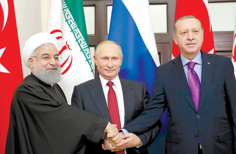 PRESIDENT HASSAN ROUHANI of Iran (left) joins hands with Russian President Vladimir Putin (center) and Turkey's President Tayyip Erdogan in Sochi, Russia (photo credit: REUTERS)