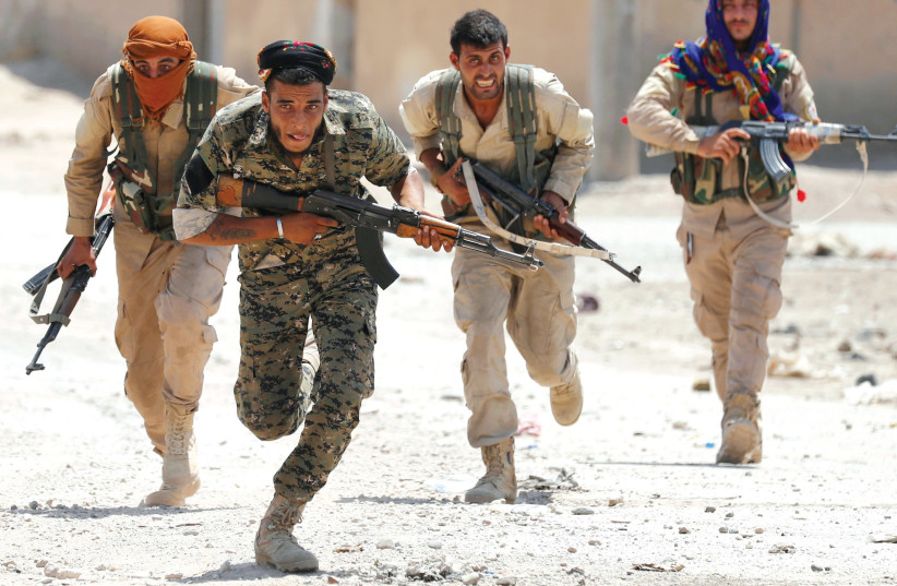 KURDISH FIGHTERS from the People's Protection Units (YPG) run across a street in Raqqa, Syria in July. (photo credit: GORAN TOMASEVIC/REUTERS)