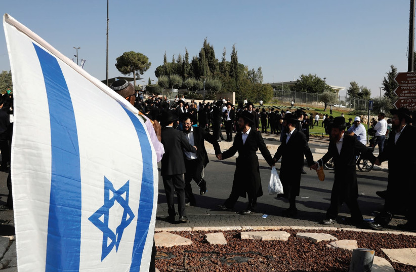 ULTRA-ORTHODOX JEWS dance as they protest outside the Knesset last month. (photo credit: REUTERS)