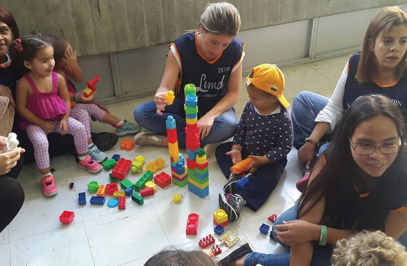 A LIMMUD volunteer entertains some of the younger attendees at the group's event in Caracas (photo credit: LIMMUD)