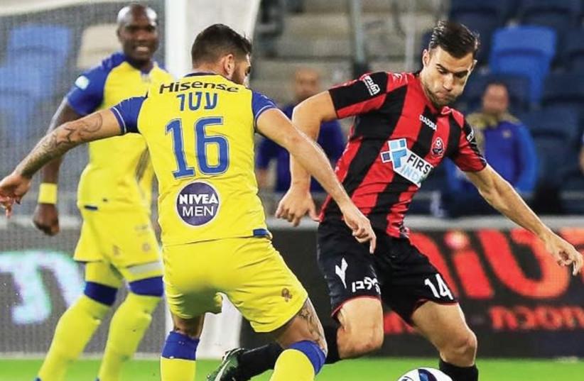 Maccabi Tel Aviv striker Eliran Atar (16) Hapoel Haifa's Radu Ginsari (right) battle for the ball in Premier League action at Haifa Stadium. (photo credit: ERAN LUF)