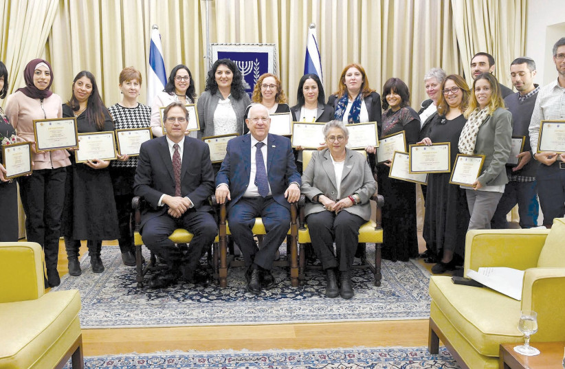 PRESIDENT REUVEN RIVLIN is flanked by his wife, Nechama, and businessman Uri Ben-Ari on at the President's Residence in Jerusalem as they pose with outstanding special education teachers recognized by Ben-Ari's Athena Fund for their innovative teaching technologies. (photo credit: MARK NEYMAN/GPO)