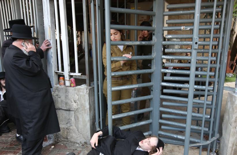 A Haredi boy blocks the exit at the IDF's Jerusalem recruiting office, November 2017 (photo credit: MARC ISRAEL SELLEM)