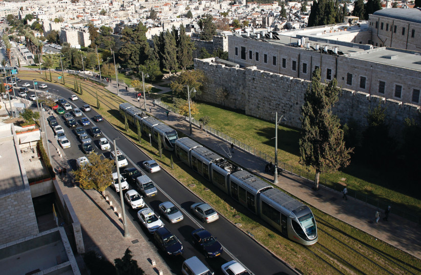 Cars come to a standstill as the light rail passes outside the walls of Jerusalem's Old City (photo credit: RONEN ZVULUN/REUTERS)