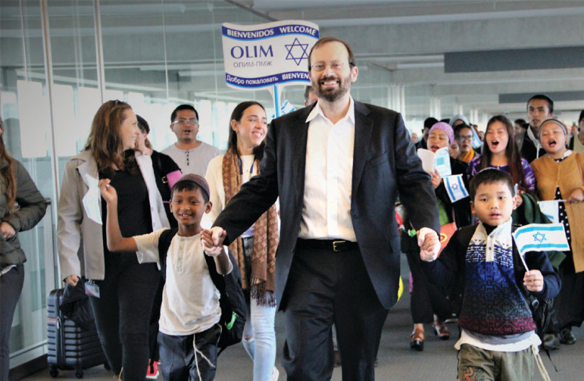 Michael Freund dances with Bnei Menashe new immigrants at Ben-Gurion Airport on November 16 (photo credit: COURTESY SHAVEI ISRAELI)
