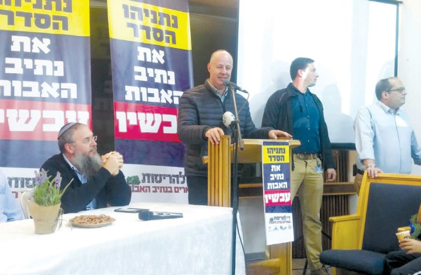 Regional Cooperation Minister Tzachi Hanegbi speaks in support of the Netiv Ha'avot outpost on Sunday night (photo credit: COURTESY NETIV HA'AVOT CAMPAIGN)