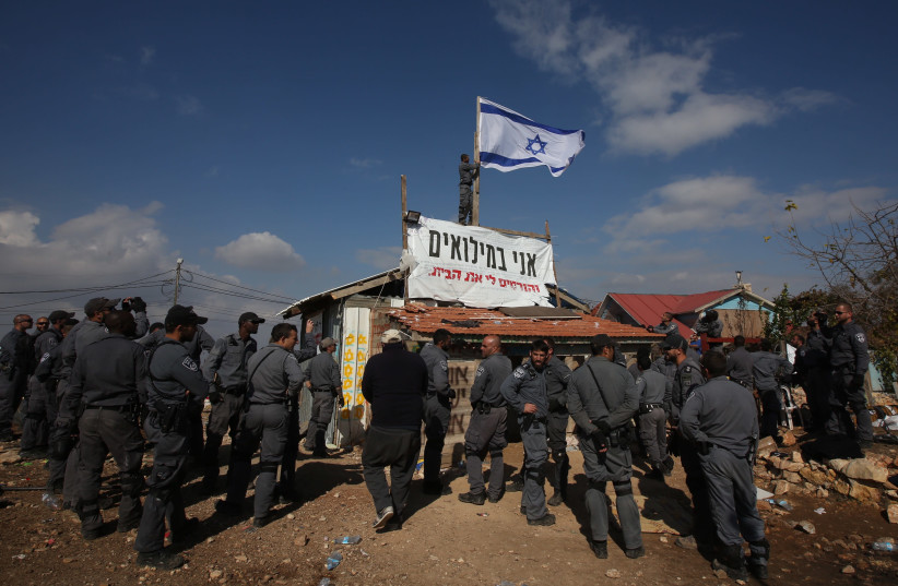 Border police remove an Israeli flag from a condemned building in Netiv Ha'avot (photo credit: MARC ISRAEL SELLEM)