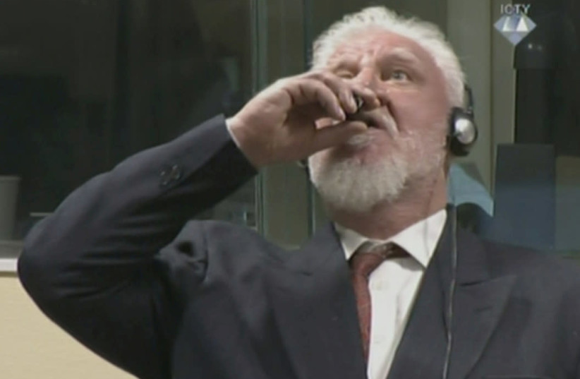 A wartime commander of Bosnian Croat forces, Slobodan Praljak, is seen during a hearing at the U.N. war crimes tribunal in the Hague, Netherlands, November 29, 2017. (photo credit: ICTY VIA REUTERS TV)