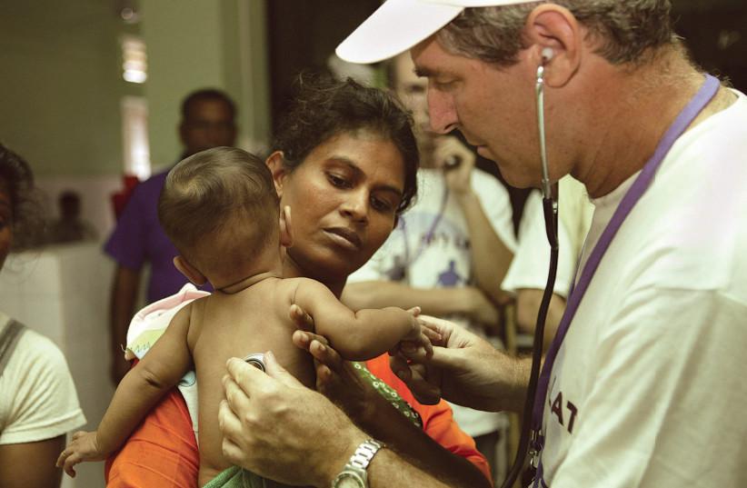 SHEBA MEDICA CENTER'S Prof. Eli Schwartz, a world specialist in tropical diseases, treats a child in Sri Lanka following the 2004 tsunami (photo credit: Courtesy)