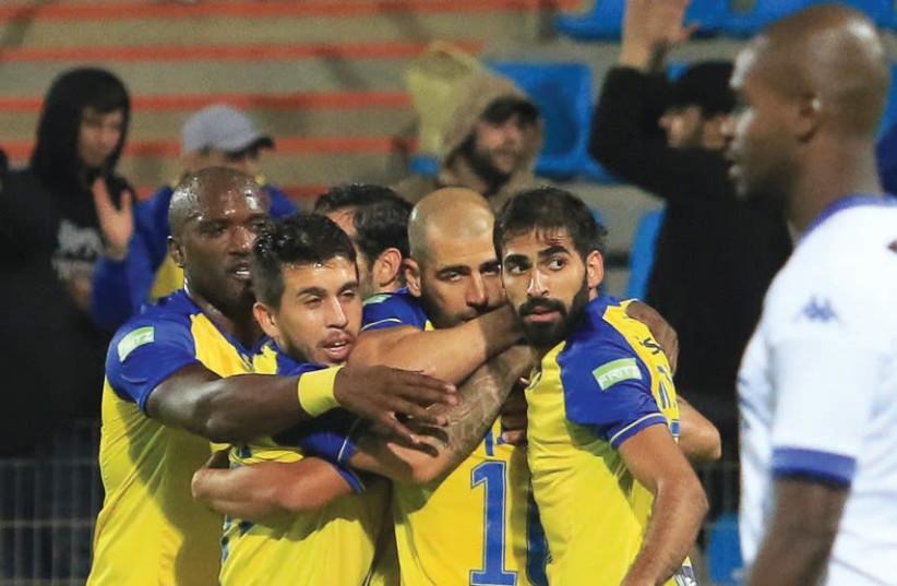 Maccabi Tel Aviv players celebrate after sealing a 2-0 win over Ironi Kiryat Shmona in the Toto Cup semifinals in Acre (photo credit: ERAN LUF)