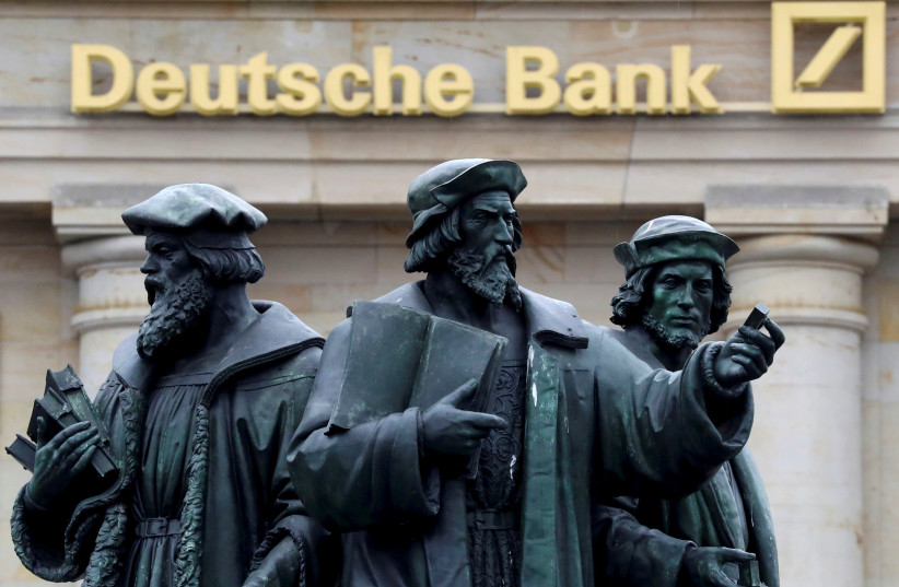 A statue is pictured next to the logo of Germany's Deutsche Bank in Frankfurt, Germany. (photo credit: REUTERS)