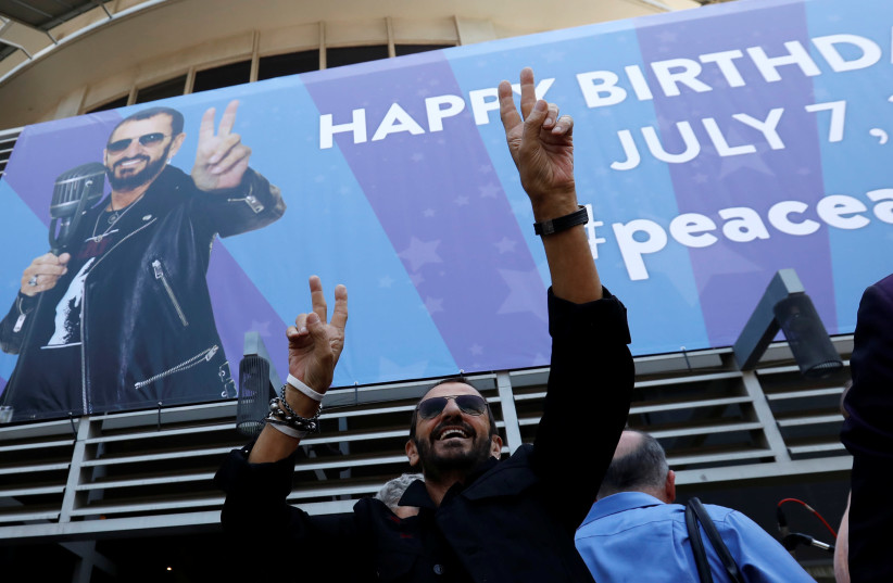 Musician Ringo Starr gestures at fans at a 'Peace & Love' event to celebrate Starr's 77th birthday in Los Angeles, California. (photo credit: REUTERS)