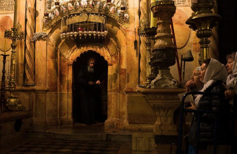 Worshippers stand nearby as a priest peers out from the Edicule, the burial place housing the purported tomb of Jesus, at the Church of the Holy Sepulchre in Jerusalem's Old City November 3, 2017 (photo credit: REUTERS/Ronen Zvulun)
