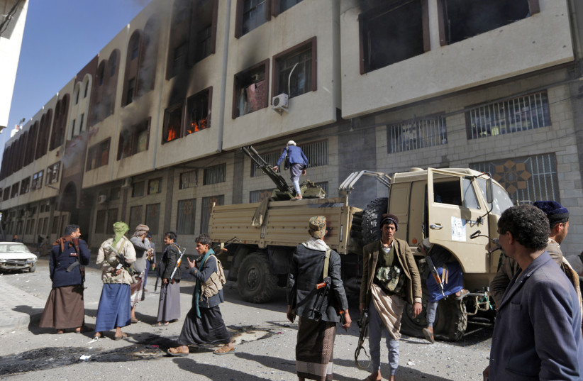 Houthi rebel righters in front of the residence of Yemen's former President Ali Abdullah Saleh after he was reported killed (photo credit: MOHAMMED HUWAIS/ AFP PHOTO)