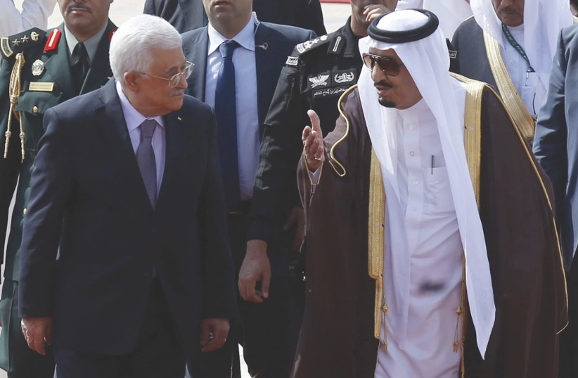 Saudi Arabia's King Salman bin Abdulaziz Al Saud walks with Palestinian President Mahmoud Abbas during a reception ceremony in Riyadh in 2015. (photo credit: REUTERS/FAISAL AL NASSER)