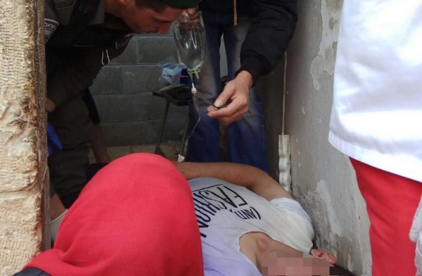 Israeli Border Police treating a Palestinian man who fell unconscious in Hebron. (photo credit: ISRAEL BORDER POLICE SPOKESMAN)