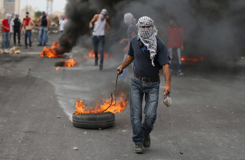 A Palestinian protester drags a burning tyre during clashes with Israeli troops near the Jewish settlement of Bet El, near the West Bank city of Ramallah October 23, 2015. (photo credit: MOHAMAD TOROKMAN/REUTERS)