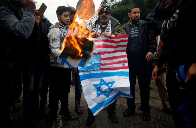 Palestinians burn signs depicting an Israeli flag and a U.S. flag during a protest against the U.S. intention to move its embassy to Jerusalem and to recognize the city of Jerusalem as the capital of Israel, in Gaza City December 6, 2017. (photo credit: MOHAMMED SALEM/REUTERS)