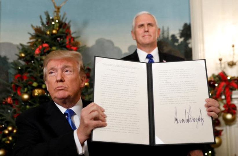 U.S. Vice President Mike Pence stands behind as U.S. President Donald Trump holds up the proclamation he signed that the United States recognizes Jerusalem as the capital of Israel and will move its embassy there, during an address from the White House in Washington, U.S., December 6, 2017 (photo credit: KEVIN LAMARQUE/REUTERS)