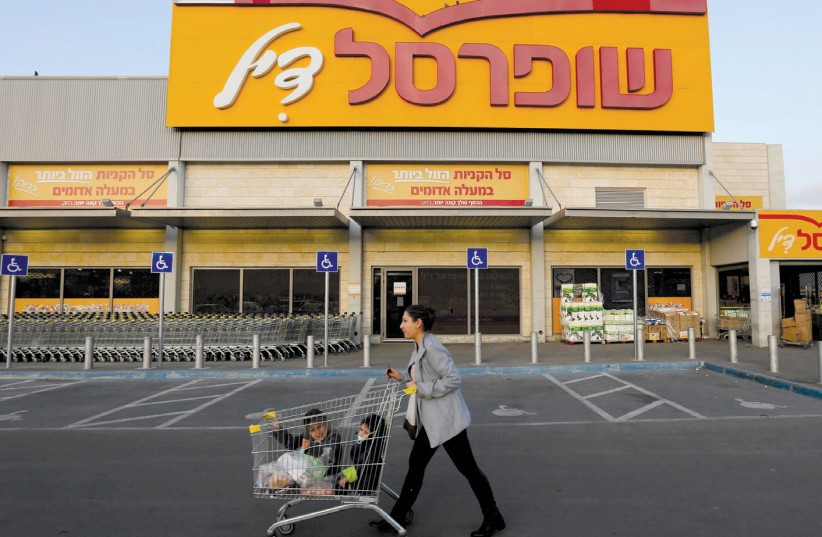A WOMAN pushes children in a shopping cart in front of a Shufersal 'Sheli' in Ma'aleh Adumim (photo credit: AMMAR AWAD/REUTERS)