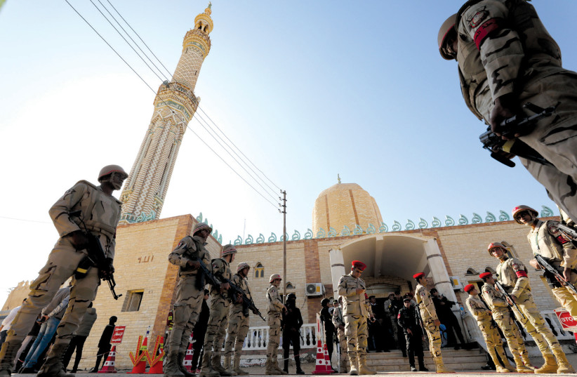 EGYPTIAN SOLDIERS watch over worshipers outside Al Rawdah mosque earlier this month after the deadly November 24 terrorist attack in Bir Al-Abed, Egypt (photo credit: MOHAMED ABD EL GHANY/REUTERS)