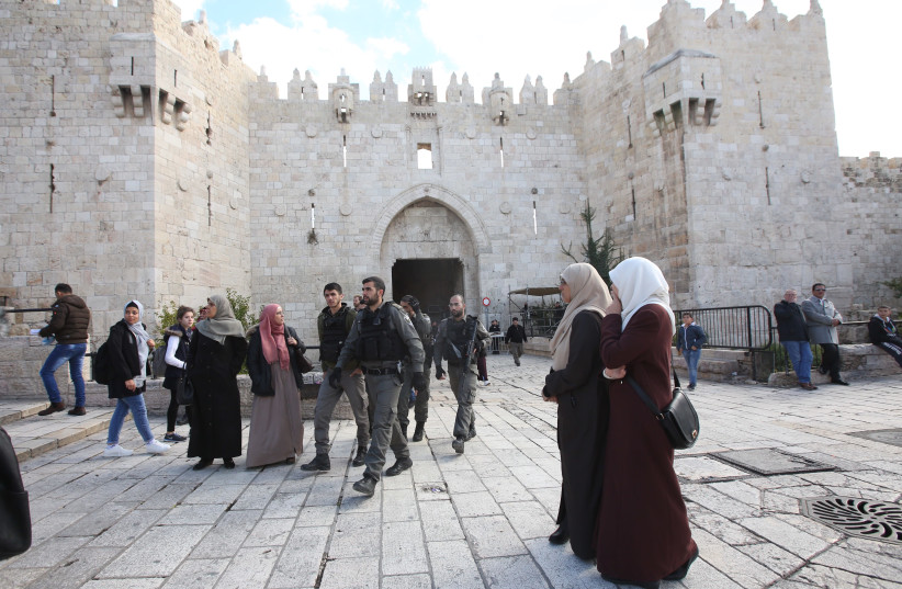 Muslim women and Israeli security forces outside the Damascus Gate in the Old City of Jerusalem. (photo credit: MARC ISRAEL SELLEM)