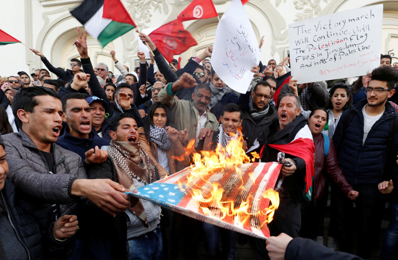 Protesters burns a US flag during a protest against Trump's decision to recognise Jerusalem as the capital of Israel, in Tunis, Tunisia, December 7, 2017.  (photo credit: ZOUBEIR SOUISSI / REUTERS)