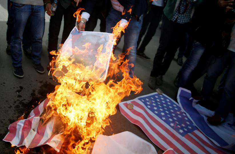 Palestinian protesters burn a poster depicting US President Donald Trump and a representation of a US flag during a protest against Trump's decision to recognize Jerusalem as the capital of Israel, in Gaza City  (photo credit: MOHAMMED SALEM/ REUTERS)