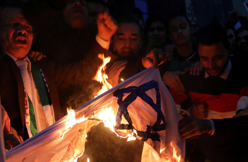 People shout slogans against Israel while burning a makeshift Israeli flag during a protest against Trump's Jerusalem declaration, in front of the Syndicate of Journalists in Cairo, Egypt December 7, 2017.  (photo credit: MOHAMED ABD EL GHANY/REUTERS)