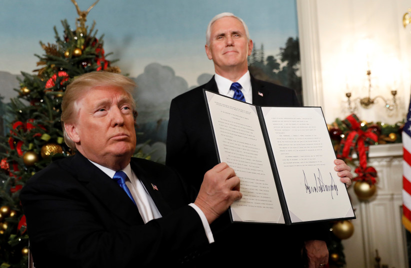 After signing, US President Donald Trump holds up the proclamation that the United States recognizes Jerusalem as the capital of Israel and will move its embassy there, during an address from the White House in Washington, US, December 6, 2017. (photo credit: REUTERS)