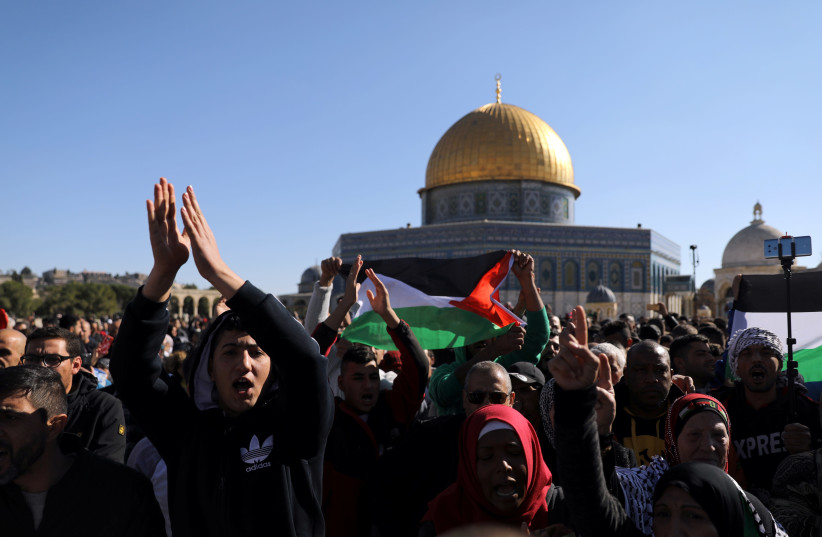 Worshippers chant as they wave Palestinian flags after Friday prayers on the compound known to Muslims as Noble Sanctuary and to Jews as Temple Mount in Jerusalem's Old City (photo credit: AMMAR AWAD / REUTERS)