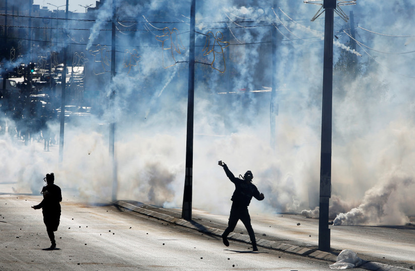 """A Palestinian protester hurls stones as tear gas is fired by Israeli troops during clashes as Palestinians call for a """"day of rage"""" in response to US President Donald Trump's recognition of Jerusalem as Israel's capital, in the West Bank city of Bethlehem December 8, 2017  (photo credit: MUSSA QAWASMA / REUTERS)"""