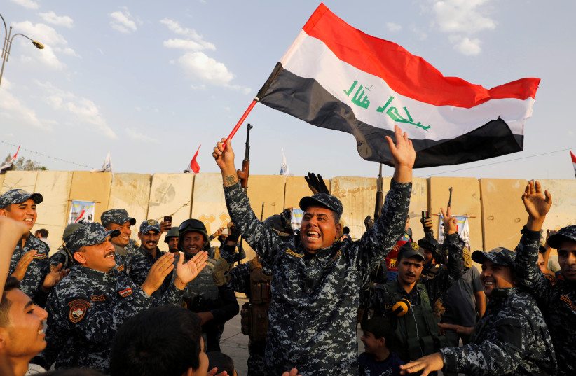 A member of Iraqi Federal Police waves an Iraqi flag as they celebrate victory of military operations against the Islamic State militants in West Mosul, Iraq July 2, 2017 (photo credit: REUTERS)
