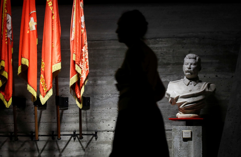 A woman walks past a bust of Soviet leader Joseph Stalin in an exhibit dedicated to the Battle of Stalingrad (photo credit: REUTERS/MAXIM SHEMETOV)