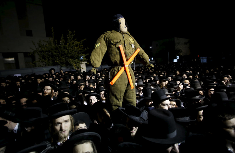 Ultra-Orthodox Jews attend a protest against a law calling for members of their community to serve in the army. (photo credit: REUTERS)
