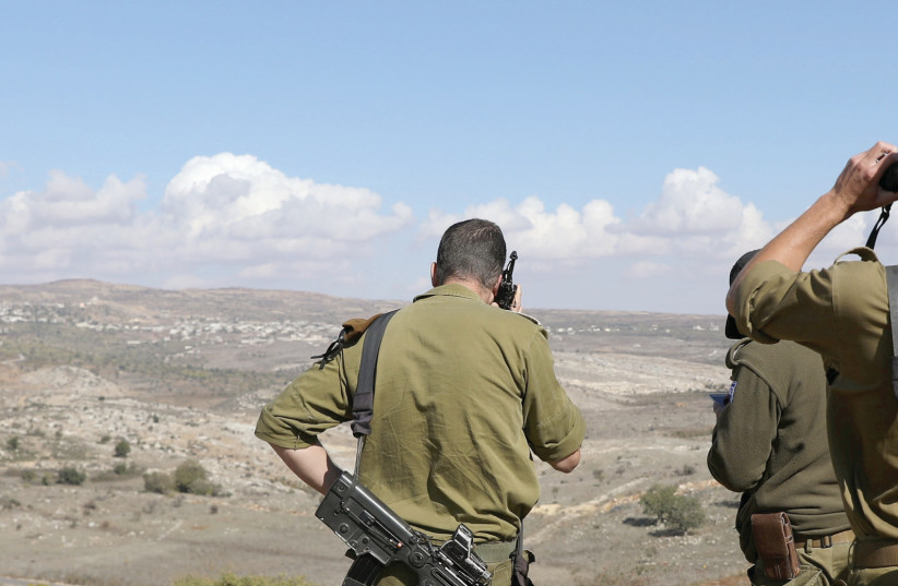 IDF soldiers look over a border fence between the Israeli side of the Golan Heights and Syria (photo credit: AMMAR AWAD/REUTERS)