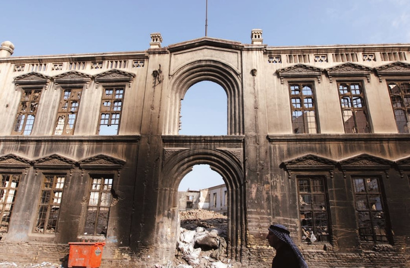 AN IRAQI RESIDENT walks past an old building destroyed during an electrical fire in Baghdad in 2011. (photo credit: REUTERS)