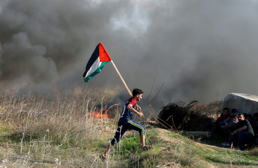 """A protester holds a Palestinian flag as he runs during clashes with Israeli troops as Palestinians call for a """"day of rage"""" in response to US President Donald Trump's recognition of Jerusalem as Israel's capital (photo credit: MOHAMMED SALEM/REUTERS)"""