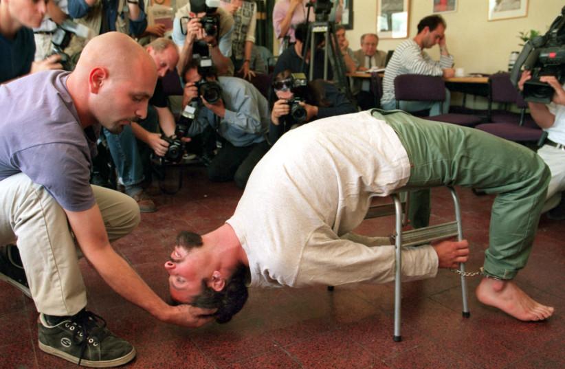 "Actors demonstrate the Israeli Shin Bet torture method known as ""Banana b'kiseh"" (photo credit: DAVID SILVERMAN / REUTERS)"