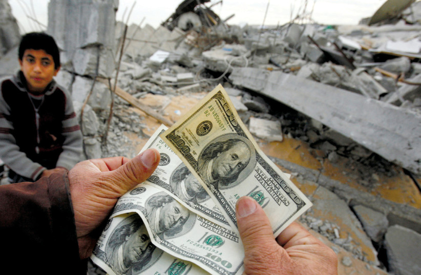 A PALESTINIAN whose house was destroyed by an Israeli air strike shows money distributed by Hamas in Jabalya in the northern Gaza Strip in 2009 (photo credit: SUHAIB SALEM / REUTERS)