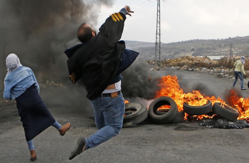 Palestinians throw stones at Israeli soldiers at a riot near Ramallah, December 2017 (photo credit: ABBAS MOMANI / AFP)
