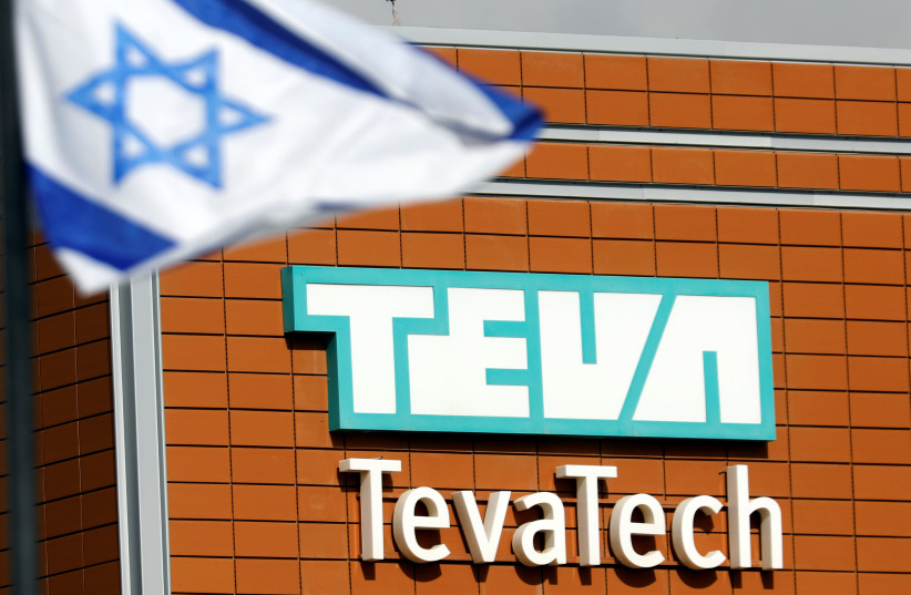 An Israeli flag flutters near the logo of Teva Tech which is part of Teva Pharmaceutical Industries in Neot Hovav, southern Israel December 14, 2017. (photo credit: REUTERS/AMIR COHEN)
