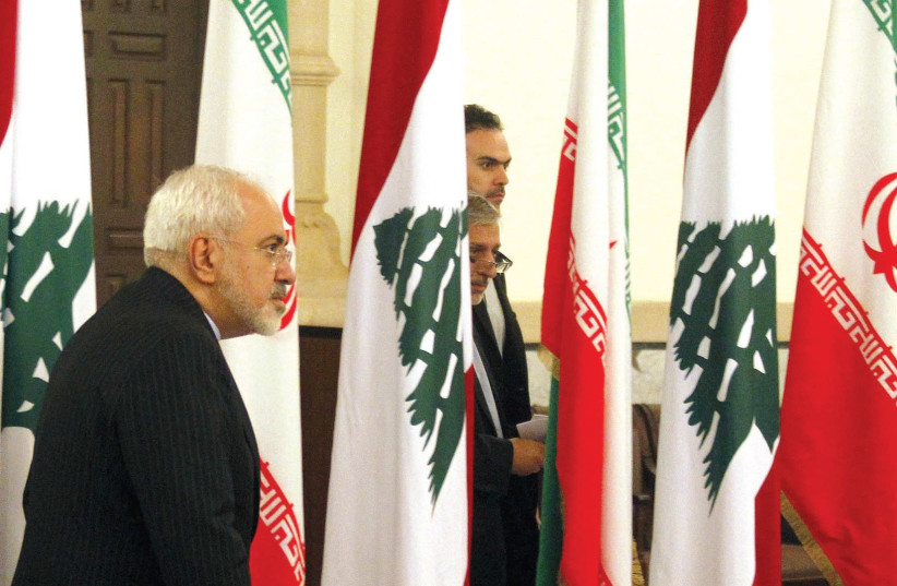 IRANIAN FOREIGN Minister Mohammad Javad Zarif walks near Lebanese and Iranian flags upon his arrival at the Government Palace in Beirut in 2015.  (photo credit: REUTERS)