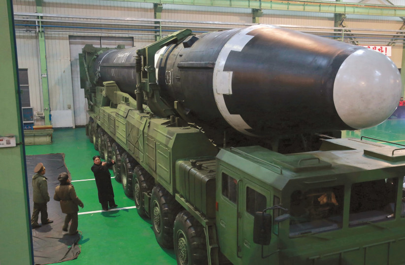NORTH KOREA'S leader Kim Jong Un gestures beside the newly developed intercontinental ballistic rocket Hwasong-15, in an undated photo released by North Korea's Korean Central News Agency in November. (photo credit: REUTERS)
