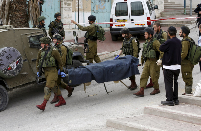 Israeli soldiers carry the dead body of one of two Palestinians, whom the Israeli military said were shot dead by Israeli troops after they attacked an Israeli soldier, in Tal Rumaida in the West Bank city of Hebron March 24, 2016.  (photo credit: REUTERS)