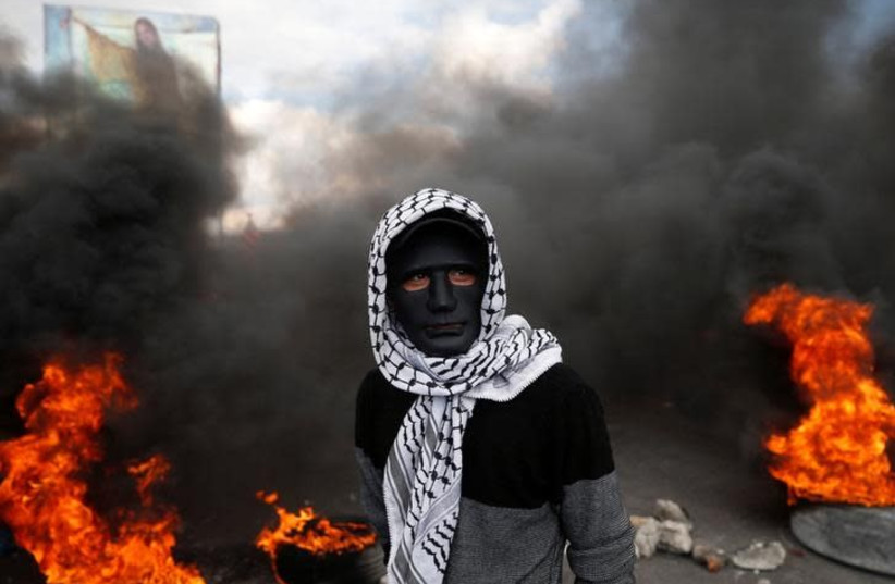 A Palestinian demonstrator stands near burning tires during clashes with Israeli troops at a protest against US President Donald Trump's decision to recognise Jerusalem as the capital of Israel, near the West Bank city of Nablus December 15, 2017 (photo credit: REUTERS/MOHAMAD TOROKMAN)