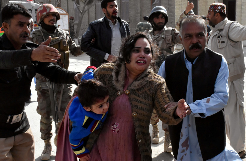 A policeman guides a family after after gunmen attacked the Bethel Memorial Methodist Church in Quetta, Pakistan (photo credit: REUTERS)