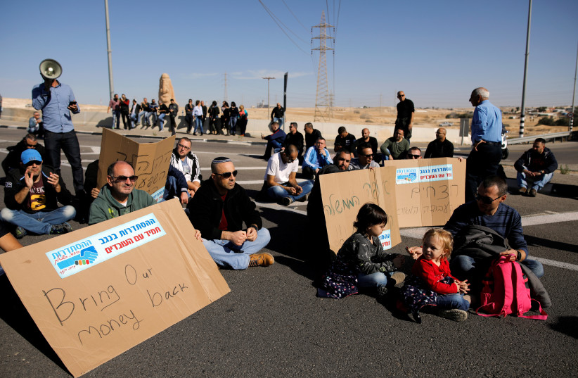 Teva Pharmaceutical Industries workers block a road during a demonstration near the facility in Neot Hovav, southern Israel December 17, 2017 (photo credit: REUTERS/AMIR COHEN)