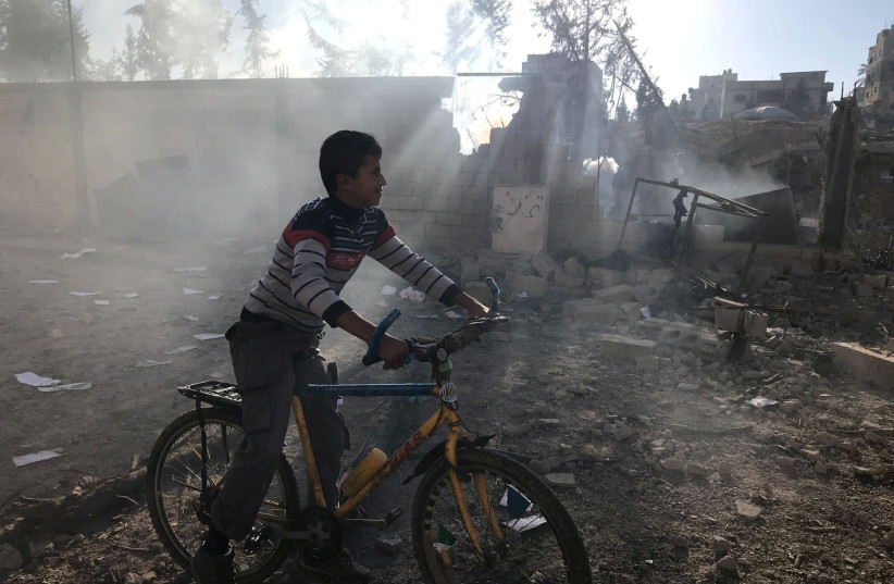 A Palestinian boy rides a bicycle near a militant target that was hit in an Israeli airstrike in the northern Gaza Strip (photo credit: MOHAMMED SALEM/REUTERS)