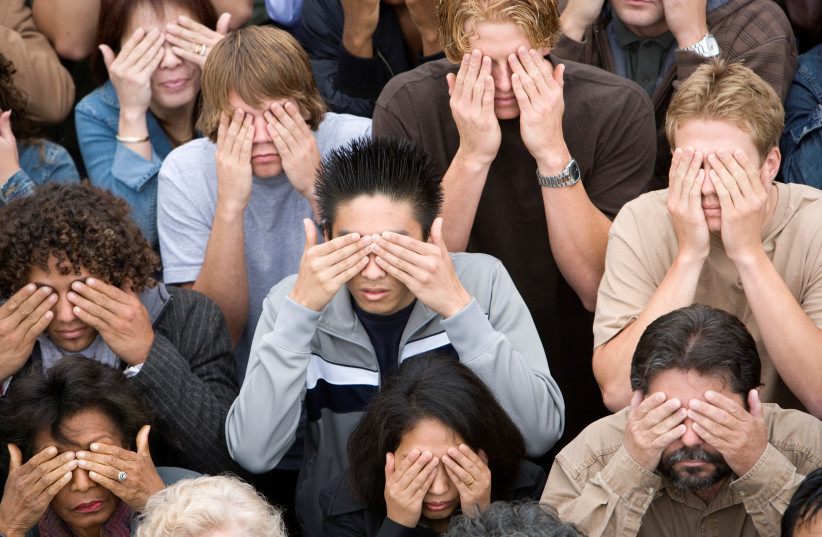 A crowd of people covering their eyes. (illustrative) (photo credit: INGIMAGE)